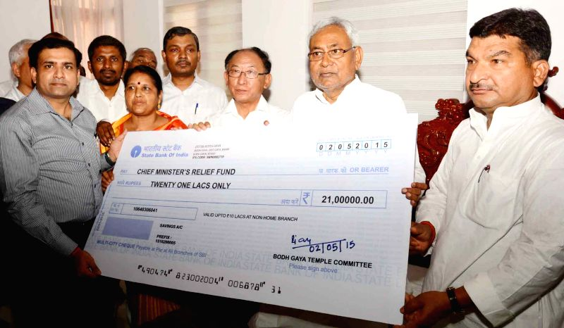 Bodh Gaya: Bodhgaya Temple Management Committee (BTMC) representatives handover a cheque to Bihar Chief Minister Nitish Kumar towards the relief of the victims of Nepal earthquake  in Bodh Gaya, on ... - Nitish Kumar
