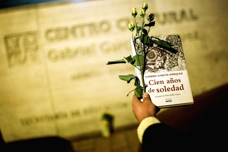 A man holds flowers and a book of the Colombian writer and journalist Gabriel Garcia Marquez in Bogota, capital of Colombia, on April 17, 2014. Gabriel Garcia ...