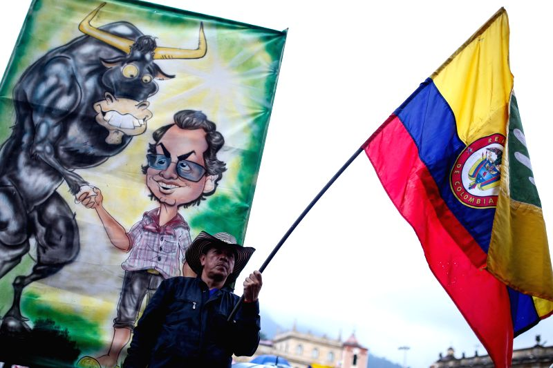 A man holds a Colombian national flag during a march for the restitution of Bogota's Mayor Gustavo Petro, in Bogota, Colombia, on April 23, 2014. Colombian ...
