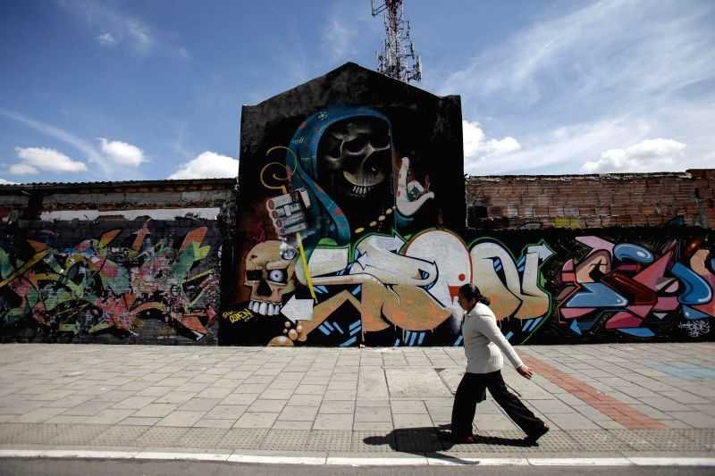 Image taken on Jan. 28, 2015 shows a resident walking past a mural in Bogota City, Colombia. In recent years the art of graffiti and mural has become an essential ...