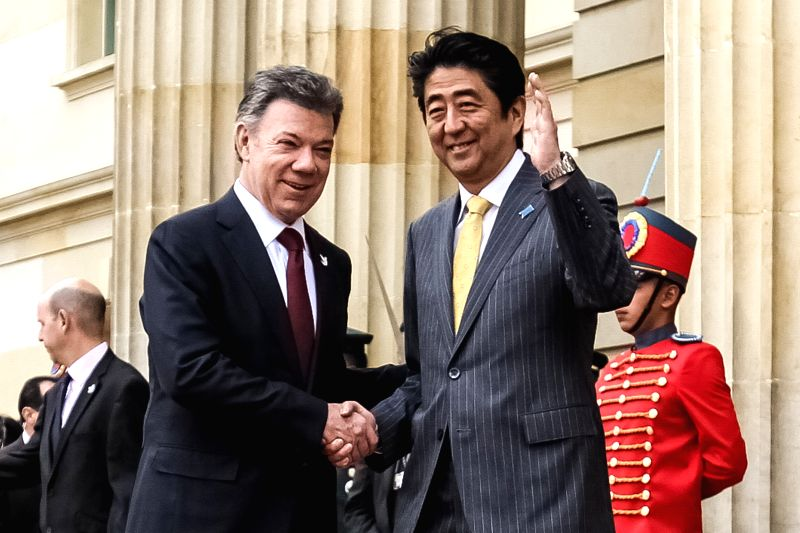 The Colombian President Juan Manuel Santos (L) shakes hands with Japanese Prime Minister Shinzo Abe at the Presidential Palace, in the city of Bogota, capital of ...