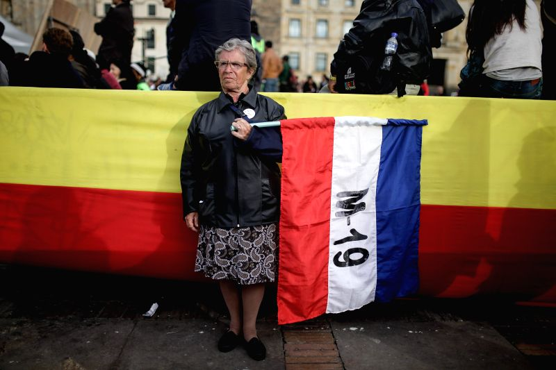 A resident holds a banner during the commemoration of the 25th anniversary of the signing of the peace agreement between the Colombian Government and the group M-19 ...