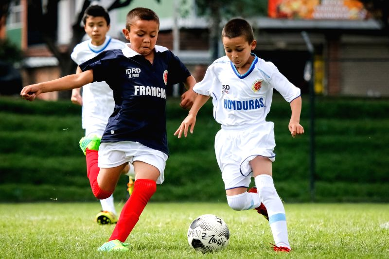 "Children compete during an event called ""Mundialito"", in a popular stadium, in Bogota, capital of Colombia, on May 11, 2014. Thousands of soccer supporters ."