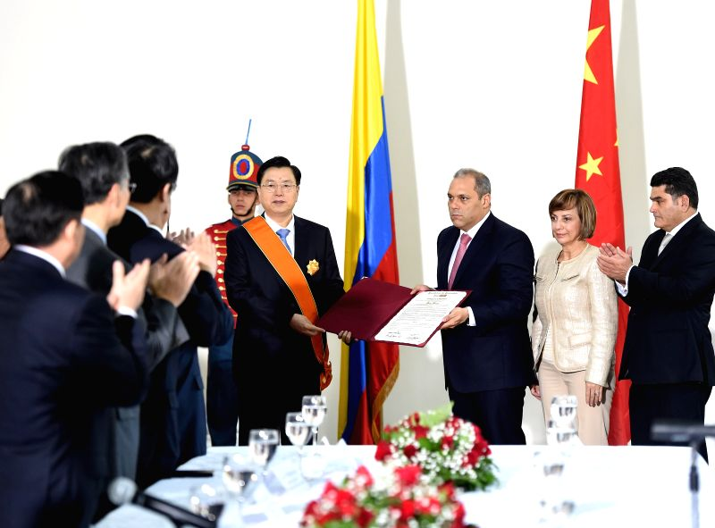 Zhang Dejiang (4th R), chairman of the Standing Committee of China's National People's Congress, is awarded a gold medal by Colombian Congress President Jose David Name Cardozo in Bogota, ...