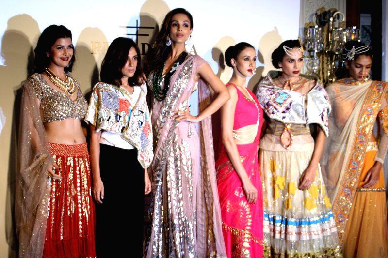 Bollywood actress Malaika Arora Khan and Nimrat Kaur pose for photos with a dress created by Indian designer Rina Dhaka at the India Couture Week 2014 in New Delhi, on July 16, 2014. - Malaika Arora Khan and Nimrat Kaur