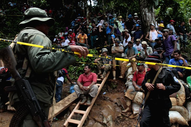 People gather in the area where a landslide took place at a mine in Bonanza Town, north Nicaragua, Aug. 29, 2014. At least 25 workers were trapped when a gold mine .