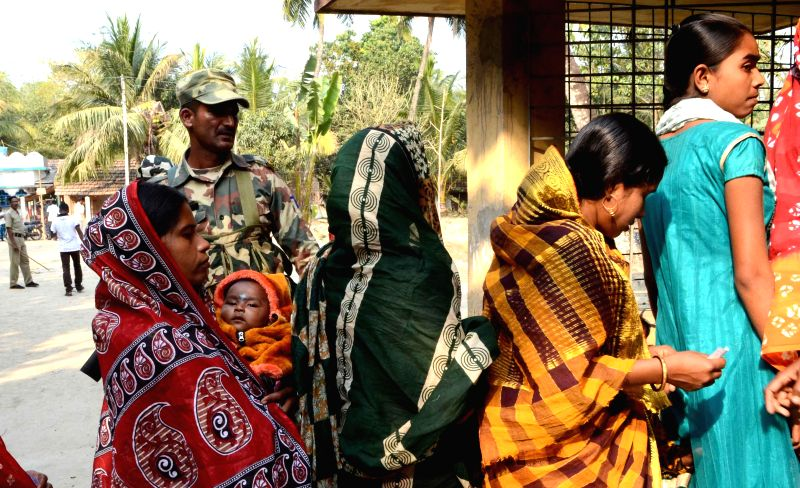 A soldier stands on guard as women queue-up to cast their votes at a polling booth during the by-elections to the Bongaon Lok Sabha constituency in North 24 Parganas district of West Bengal .