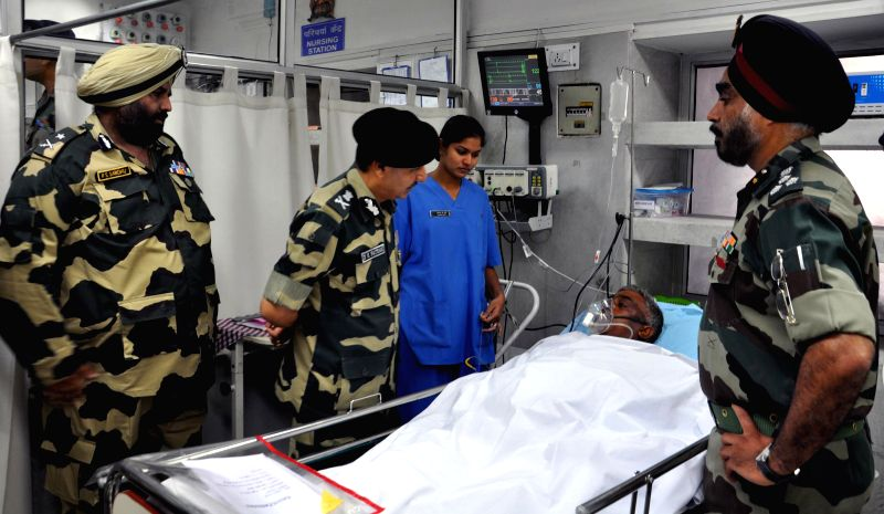 Border Security Force (BSF) Officers meet a victim of militant attack on BSF convoy at Kadalbal, Pampore, at 92 Army Base Hospital Badamibagh in Srinagar on Aug 13, 2014. Eight soldiers were injured .