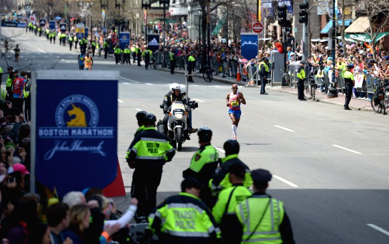 Plicemen guard along Boylston street where the 2014 Boston marathon is held, in Boston, Massachusetts, the United States, April 21, 2014.  Under protection of more .