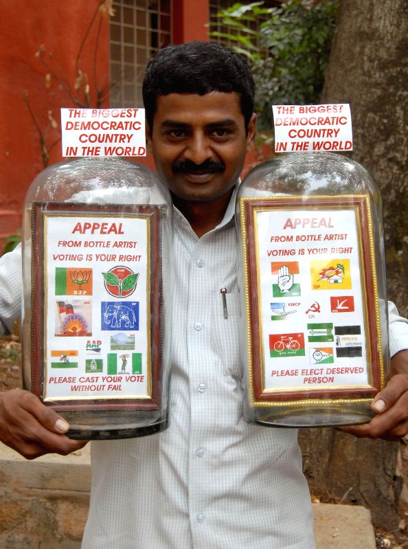 Bottle artist Basavaraj S Gowda displays his creations appealing people to vote during the 2014 Lok Sabha Elections during a press conference in Bangalore on April 15, 2014. - Basavaraj S Gowda