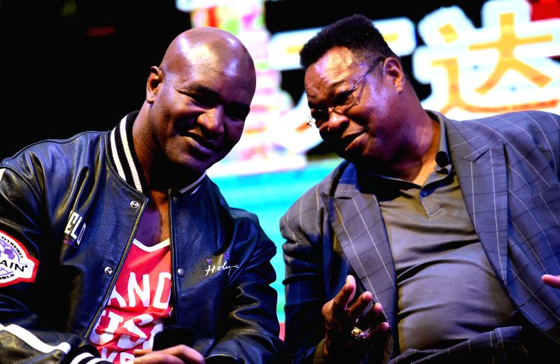 Boxing legends Evander Holyfield (L) and Larry Holmes are present at the press conference of Greater China Boxing Match before 2015 WBC annual meeting in Kunming, ...