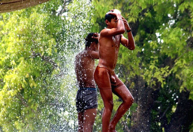 Boys cool themselves on a hot day in New Delhi on April 18, 2017.