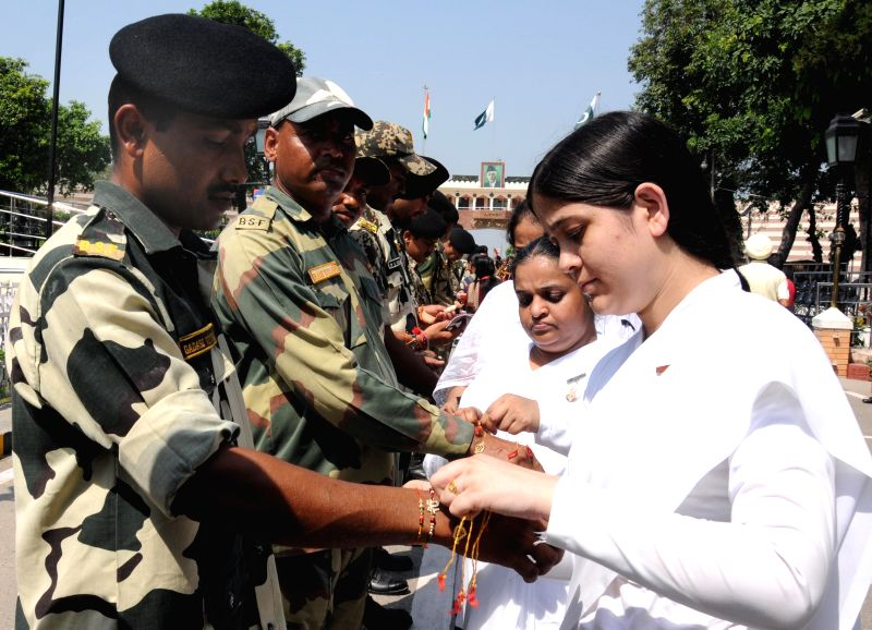 Bramha Kumaris tie rakhis on the wrist of soldiers deployed at Wagha border on Raksha Bandhan on Aug 10, 2014.