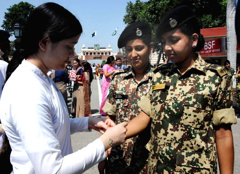 Bramha Kumaris tie rakhis on the wrist of soldiers deployed at Wagha border on Raksha Bandhan on Aug 10, 2014.