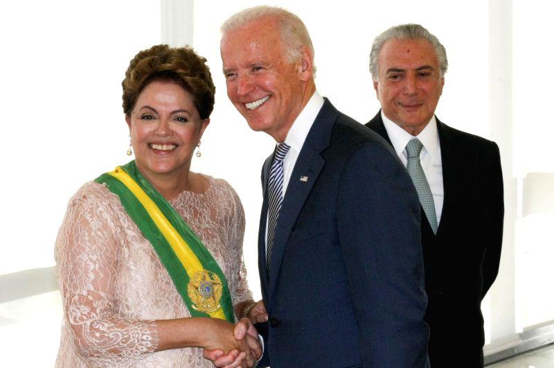 Brazilian President Dilma Rousseff (L) shakes hands with U.S. Vice President Joe Biden during the ceremony of inauguration at Palacio do Plenalto in Brasilia, ...