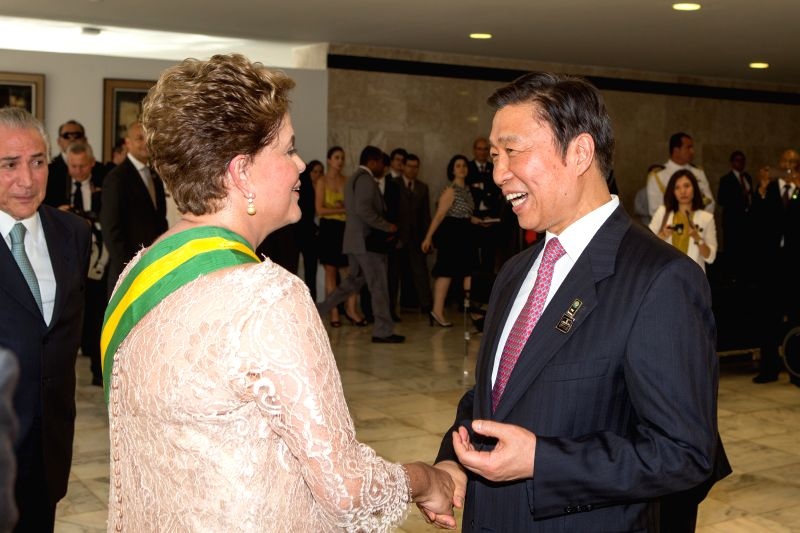 Chinese President Xi Jinping's special representative, Chinese Vice President Li Yuanchao (R) shakes hands with Brazilian President Dilma Rousseff as Li Yuanchao ...