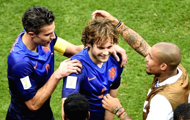 Netherlands' Daley Blind (C) celebrates with Robin van Persie (L) after scoring a goal during the third place play-off match between Brazil and Netherlands of 2014