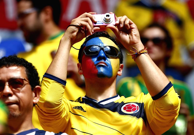 A Colombia's fan takes a photo before a Group C match between Colombia and Cote d'Ivoire of 2014 FIFA World Cup at the Estadio Nacional Stadium in Brasilia, ...