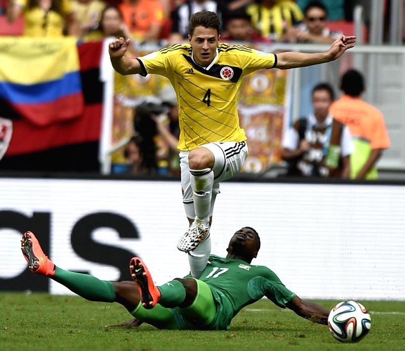 Cote d'Ivoire's Serge Aurier slide tackles the ball controlled by Colombia's Santiago Arias during a Group C match between Colombia and Cote d'Ivoire of 2014 FIFA .