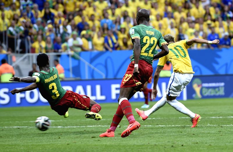 Brazil's Neymar (R) scores a goal during a Group A match between Cameroon and Brazil of 2014 FIFA World Cup at the Estadio Nacional Stadium in Brasilia, Brazil, ...