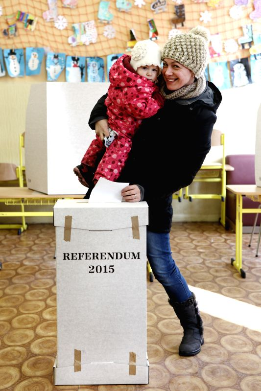 A mother casts her ballot with her child during a referendum about same-sex marriage, ban of gay and lesbian couples from adopting and sex education classes in ...