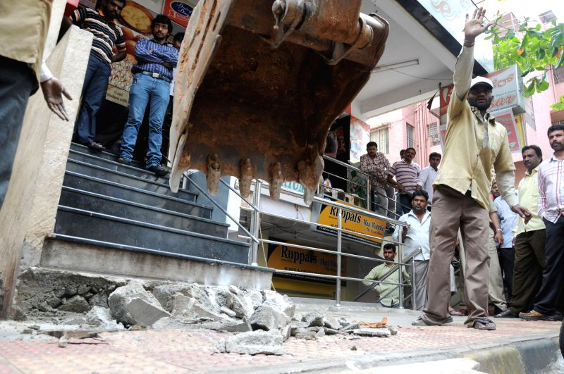 Bruhat Bangalore Mahanagara Palike (BBMP) demolishes illegal structures encroaching footpaths in Bangalore on Sept 4, 2014.