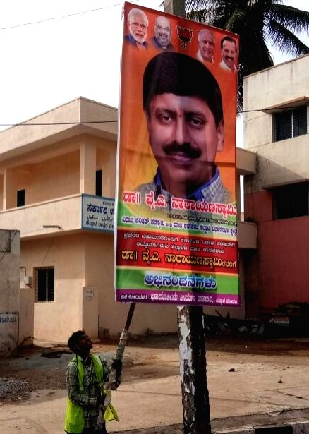 Bruhat Bengaluru Mahanagara Palike (BBMP) officials pull down the illegal flex boards and banners after the Karnataka High Court ordered to remove all illegal flex banners before the court ...