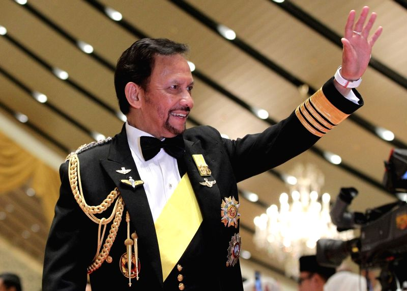 Brunei's Sultan Haji Hassanal Bolkiah waves to guests at the royal banquet celebrating his golden jubilee on the throne in Bandar Seri Begawan, capital ...