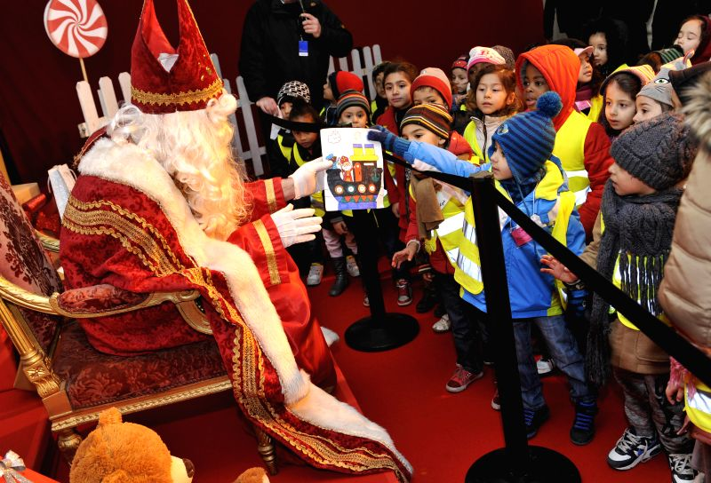 Brussels (Belgium): An acotor dressed as Saint Nicolas receives a painting from a boy during the Saint Nicolas festival in Brussels, Belgium, Dec. 5, 2014. Saint Nicolas festival traditionally ...