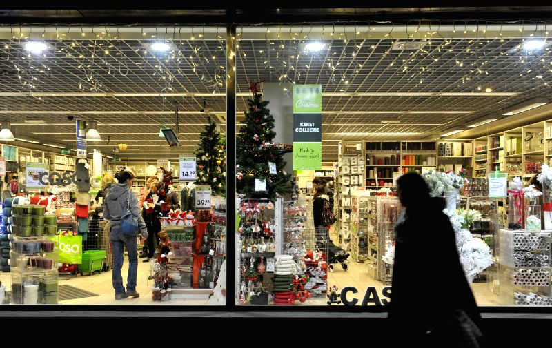 Brussels (Belgium): Photo taken on Nov. 28, 2014 shows a pedestrian passing a store selling Christmas goods in downtown Brussels, capital of Belgium. The market was opened to public here on Friday. ..