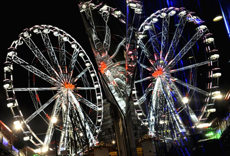 Brussels (Belgium): Photo taken on Nov. 28, 2014 shows ferris wheel is reflected on a glass window at Christmas market in downtown Brussels, capital of Belgium. The market was opened to public here ..