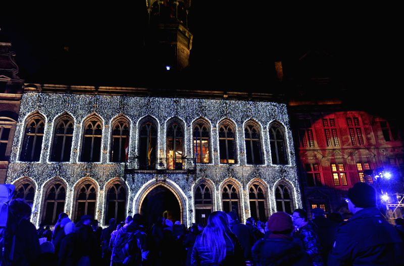 People stand in front of lights decorated city hall of Mons, Belgium, Jan. 24, 2015, during the opening ceremony of 2015 European Capital of Culture. (Xinhua/Ye ...