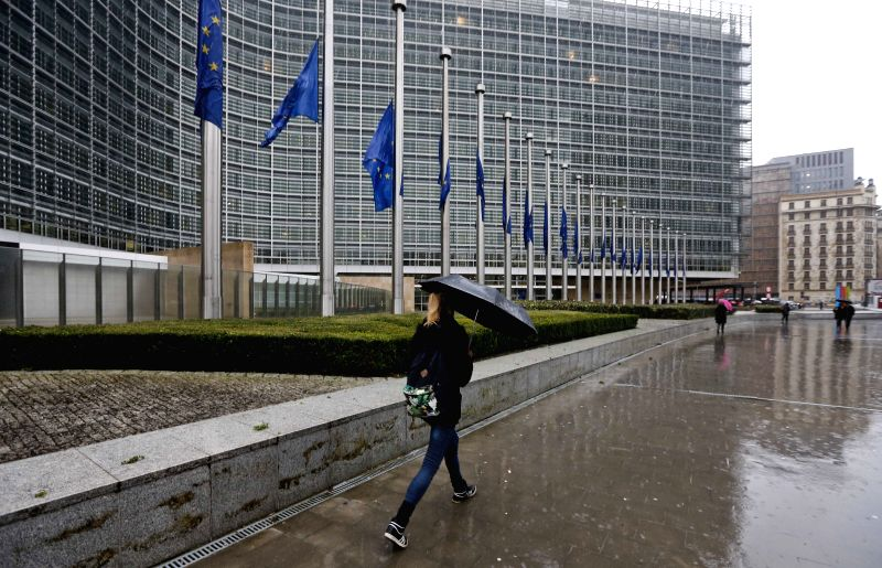 A pedestrian passes the European Commission building with the EU flags flying at half mast commemorating the victims of the January 7 attack against French magazine