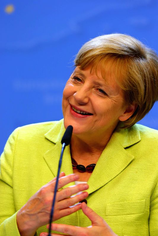 German Chancellor Angela Merkel smiles as she receives birthday wishes at a press conference after a special meeting of the European Council at the EU headquarters