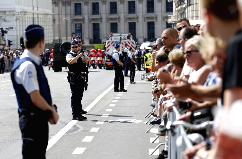 BRUSSELS, July 21, 2016 - Police guard on an avenue as visitors wait for the Military Parade to celebrate Belgium's National Day in Brussels, Belgium, July 21, 2016.