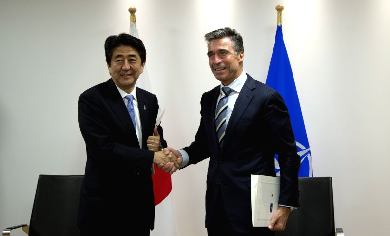 Japanese Prime Minister Shinzo Abe (L) and NATO Secretary-General Anders Fogh Rasmussen shake hands after signing the Individual Partnership and Cooperation Program .