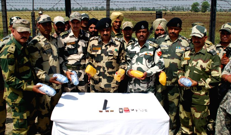 BSF officials display 8 kg of heroin recovered from alleged Pakistani smuggler who was killed in an operation near Rajata village of Punjab on April 16, 2014.