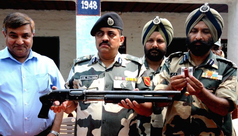 BSF officials present before press the 21 kg of heroin recovered in the Amritsar sector of the border along with an Italian-made shot-gun and Pakistan-made ammunition; on July 13, 2016.