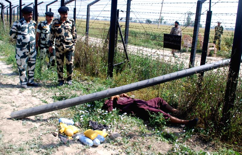BSF officials stand by the body of an alleged Pakistani smuggler from whom 8 kg heroin and a pistol were recovered near Rajata village of Punjab on April 16, 2014.