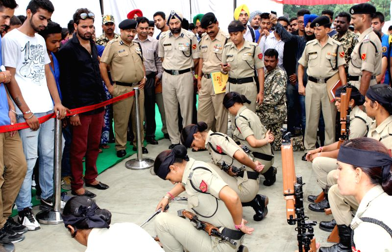 BSF personnel demonstrate X95 Assault Riffle, AK-47 and other weapons to students during an awareness program Lyallpur Khalsa College in Jalandhar on Aug 11, 2014.