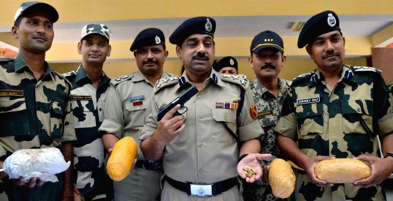 BSF personnel display 4 kg heroin along with arms and ammunition seized by them from Khasa near Amritsar on Aug 29, 2014.