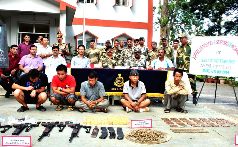 BSF personnel personnel present before media five Chakma youths along with the arms and ammunitions recovered by them in Aizawl of Mizoram on Aug 28, 2014.