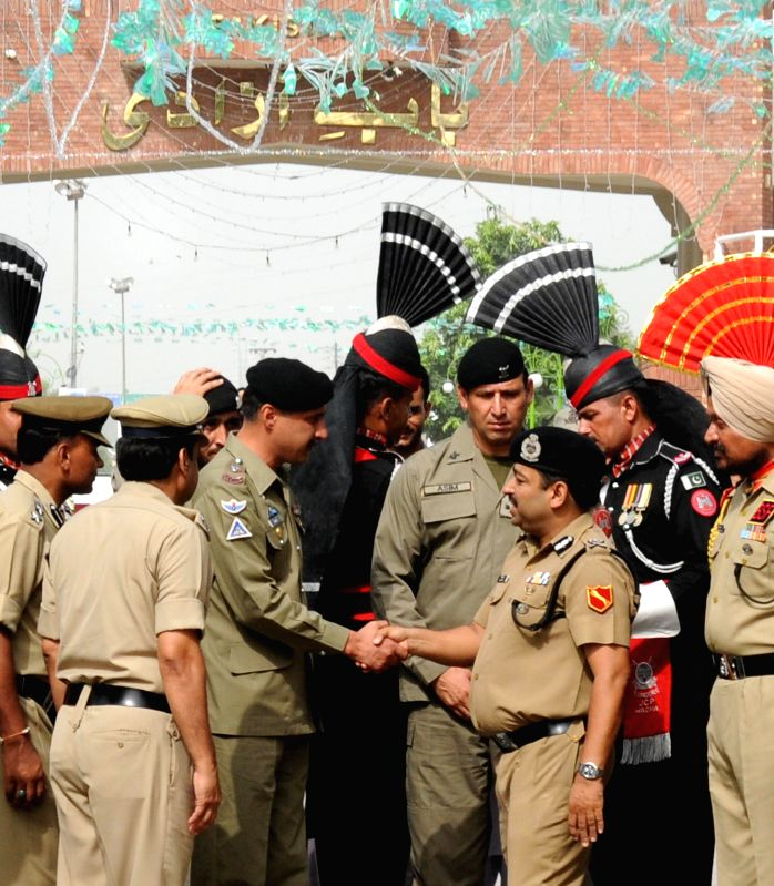 BSF Punjab frontier Inspector General (IG) Ashok Kumar shakes hands with Pakistani Rangers wing Commander Mohammad Asher Khan during 68th Independence Day celebrations near Indo-Pak border in Attari . - Ashok Kumar and Mohammad Asher Khan