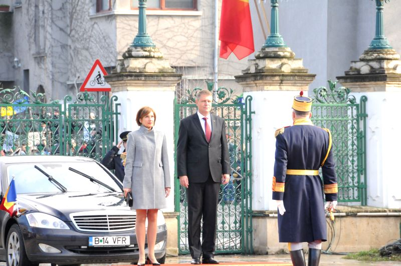 Romanian President Klaus Iohannis and his wife review the honor guard at the presidential palace in Bucharest, Romania, Dec. 21, 2014. Romanian President-elect ...