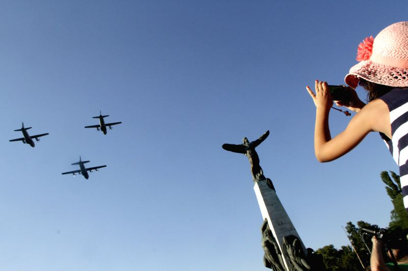 A girl takes photo for the military airplanes passing near the pilot's monument during the ceremony celebrating the Air Force Day, at the Air Heroes Monument, in .