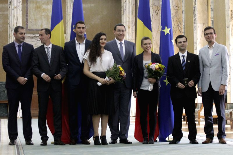 Romanian Prime Minister Victor Ponta (C) poses for a photo with six new tourism ambassadors at the Victoria Palace in Bucharest, capital of Romania, July 7, 2014. .