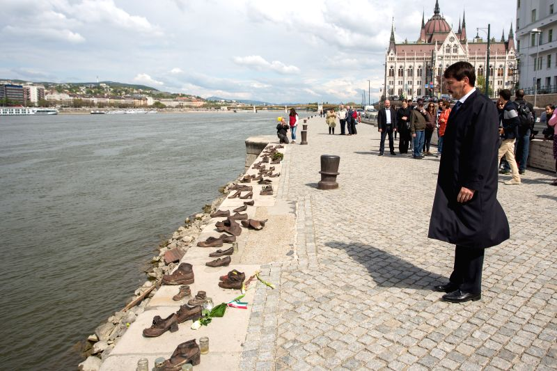 "Hungary's President Janos Ader mourns at ""Shoes on the Danube Bank"" statues to commemorate the Hungarian victims of the Holocaust in Budapest, Hungary .."