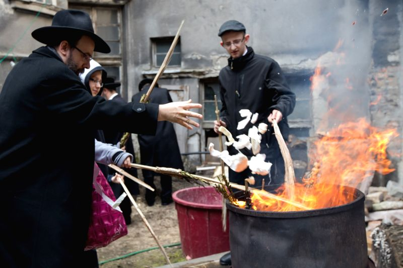 A Jewish family burns leavened foods in the final preparation for the Passover holiday in a courtyard in Budapest, Hungary, on April 3, 2015.  (Xinhua/Attila ...