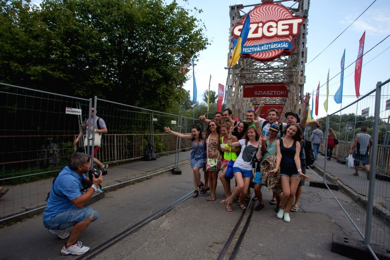 "Music fans pose for a photo at the entrance of the Sziget (Hungarian for ""Island"") festival on the Obuda Island in Budapest, Hungary, on Aug. 12, 2014. .."