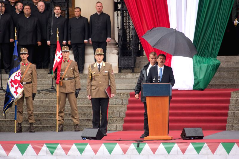 Hungarian President Janos Ader (1st R) delivers a speech in Kossuth square in front of the Hungarian Parliament building to celebrate Hungarian national holiday in